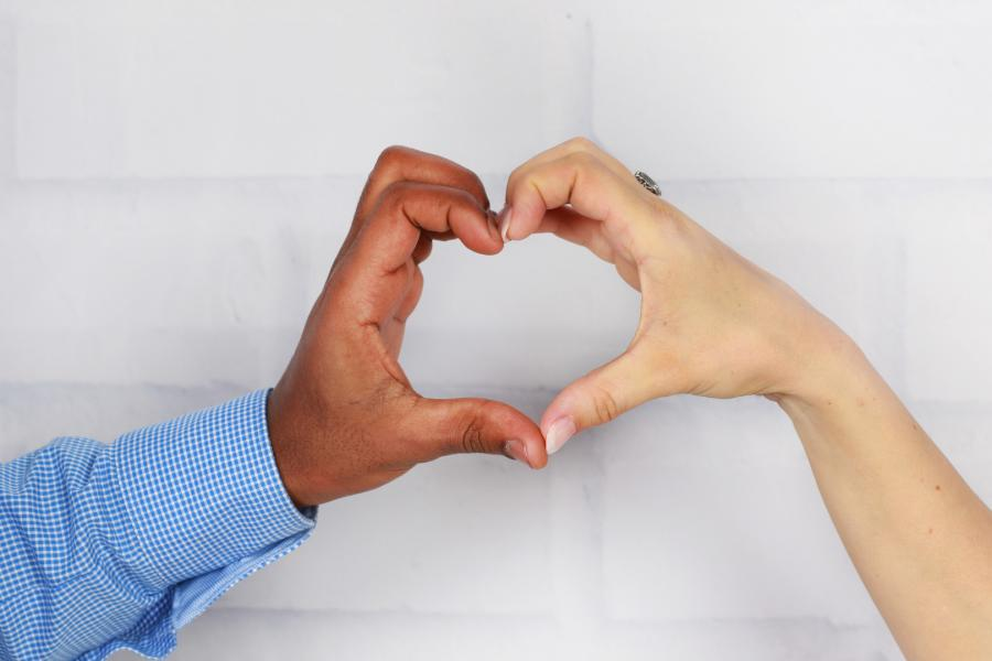 Czarny mężczyzna i biała kobieta składają dłonie w serce