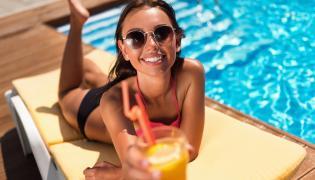 Kobieta z drinkiem nad basenie