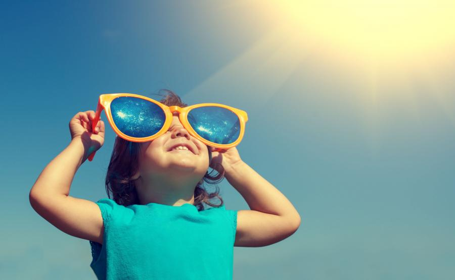 Dziecko patrzy przez okulary słoneczne prosto w słońce