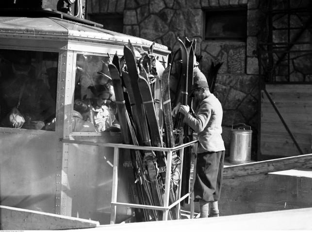 Pasażerowie w wagoniku kolejki linowej. Transport nart w platformie przymocowanej na zewnątrz wagonika