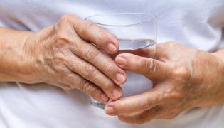 Starsza osoba trzyma szklankę z wodą
