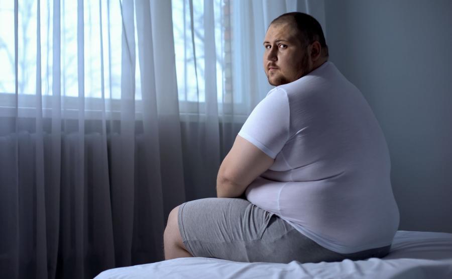 Otyły mężczyzna siedzi na łóżku
