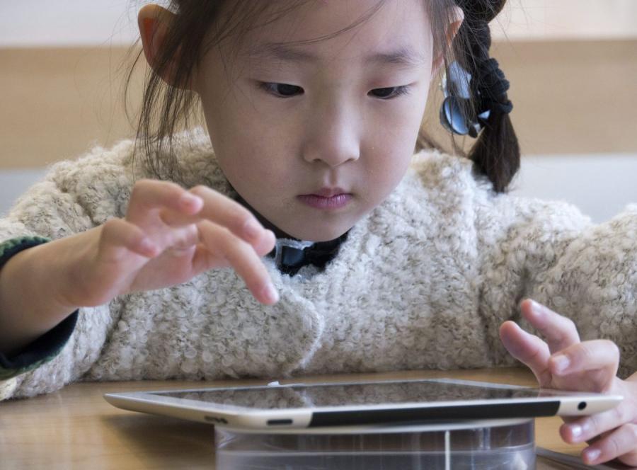 Mała dziewczynka bawi się iPadem