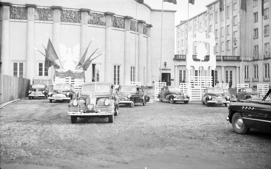 Chevrolet model z 1946 roku (wóz ochrony) prowadzi kolumnę samochodów rządowych. Z tyłu obok i za tramwajem widocznych co najmniej 6 kolejnych Chevroletów