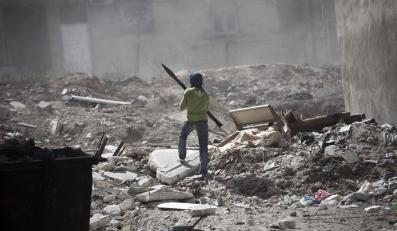 Bojownik na gruzach syryjskiego miasta