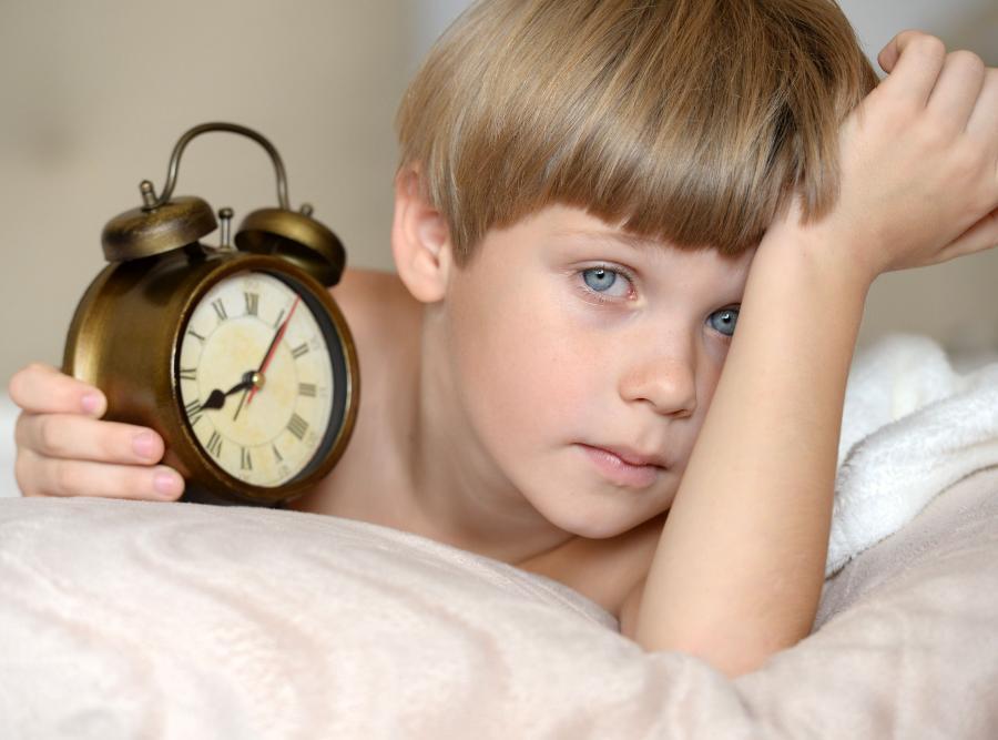 Dziecko w łóżku trzyma zegarek