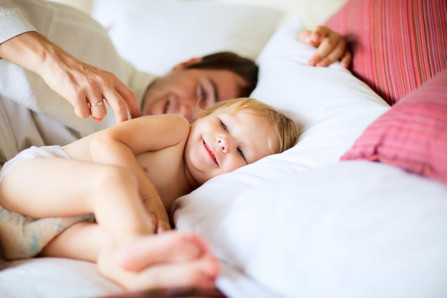 Ojciec z dzieckiem w łóżku