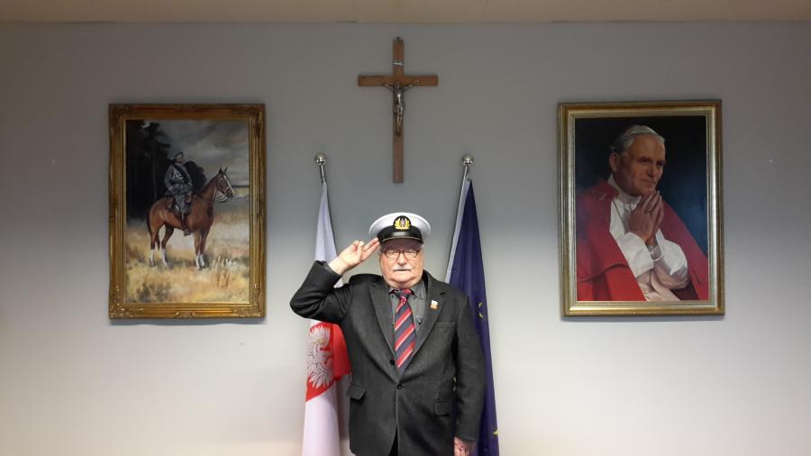 Lech Wałęsa salutuje w czapce kapitańskiej pod krzyżem, między wzierunkiem marszałka Piłsudskiego i papieża Jana Pawła II (źródło: www.wykop.pl/ludzie/lechwalesa/)