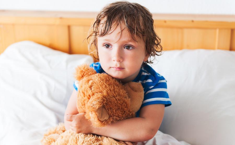 Smutne dziecko siedzi w łóżku