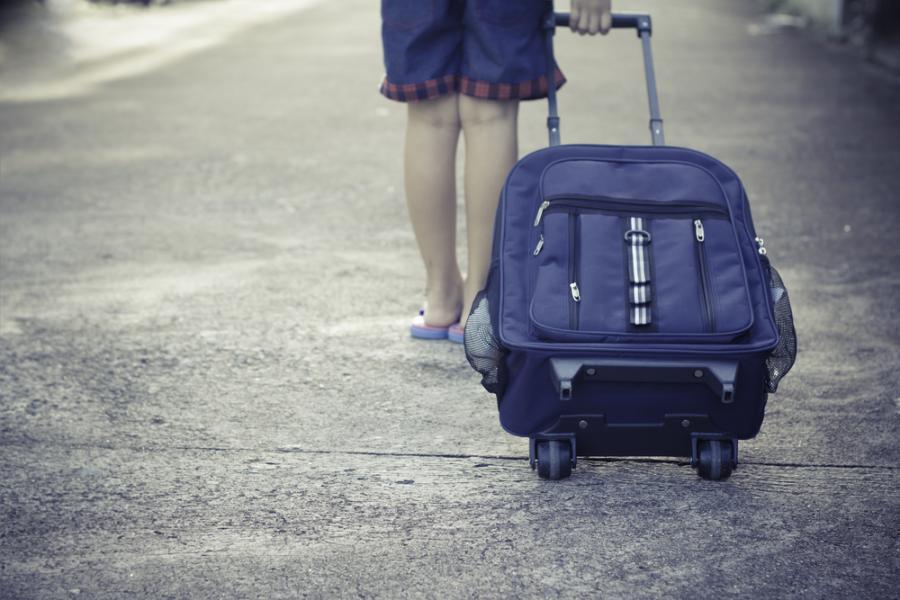 Dziecko z plecakiem na kółkach