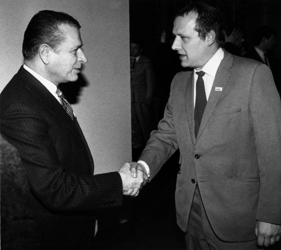 Czesław Kiszczak i Adam Michnik witają się w czasie obrad Okrągłego Stołu, 6 lutego 1989 roku